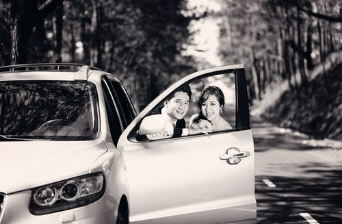 Man and Woman Behind Vehicle Door Grayscale Photo