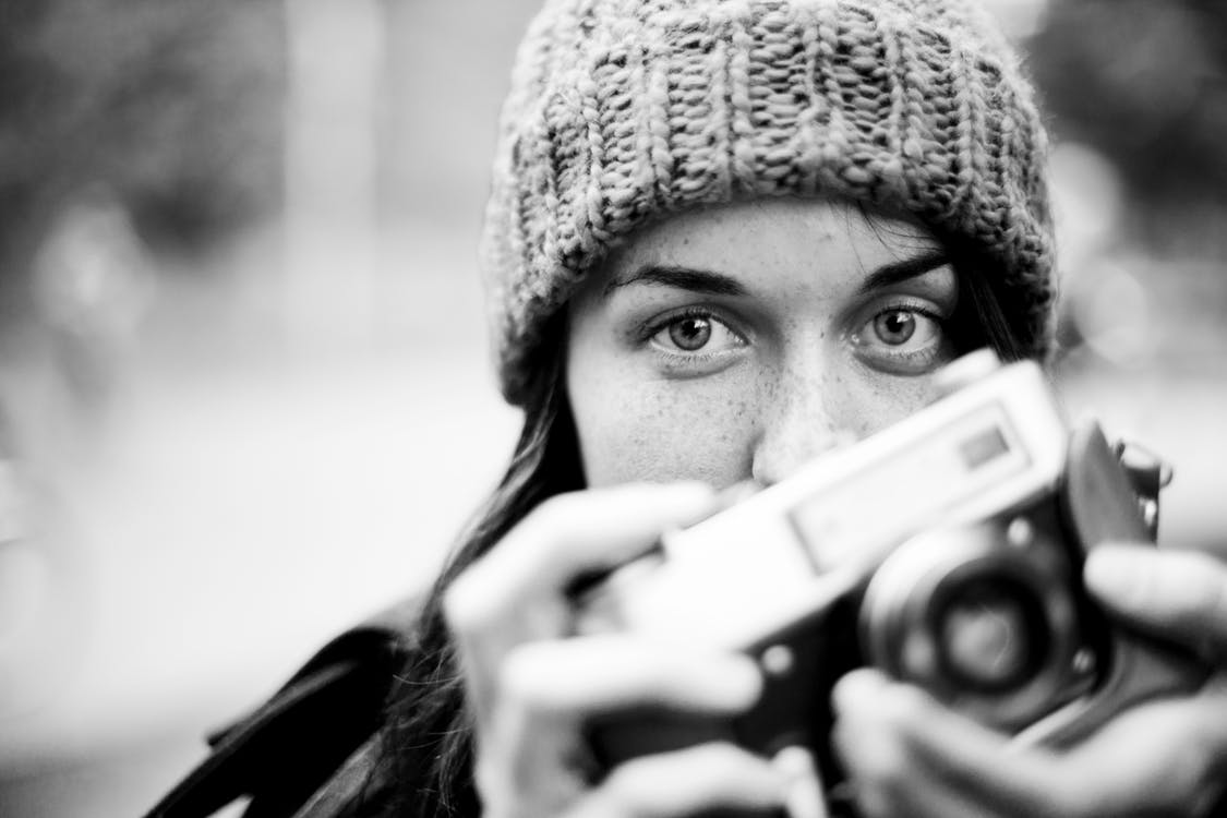 Grayscale Photography of Woman Holding Camera