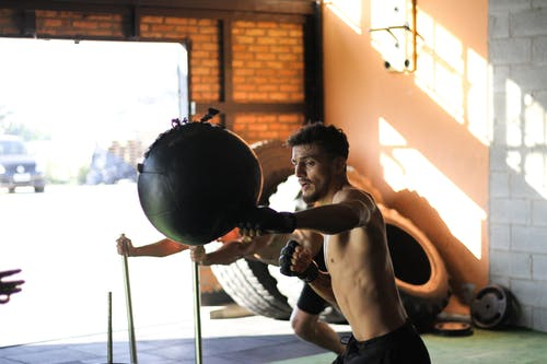 Man in Black Shorts Punching Black Ball