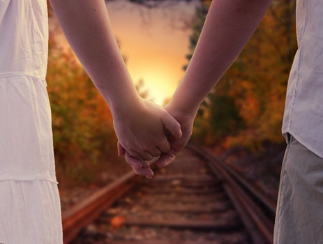 Couple Holding in Train Rails during Golden Hour
