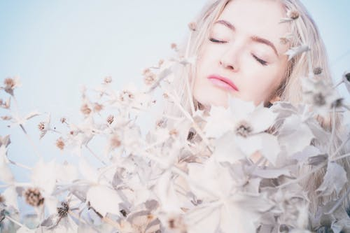 Closeup Photo of Woman Surrounded by White Petaled Flowers