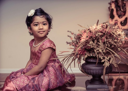 Girl Beside Flower Vase Inside White Painted Room