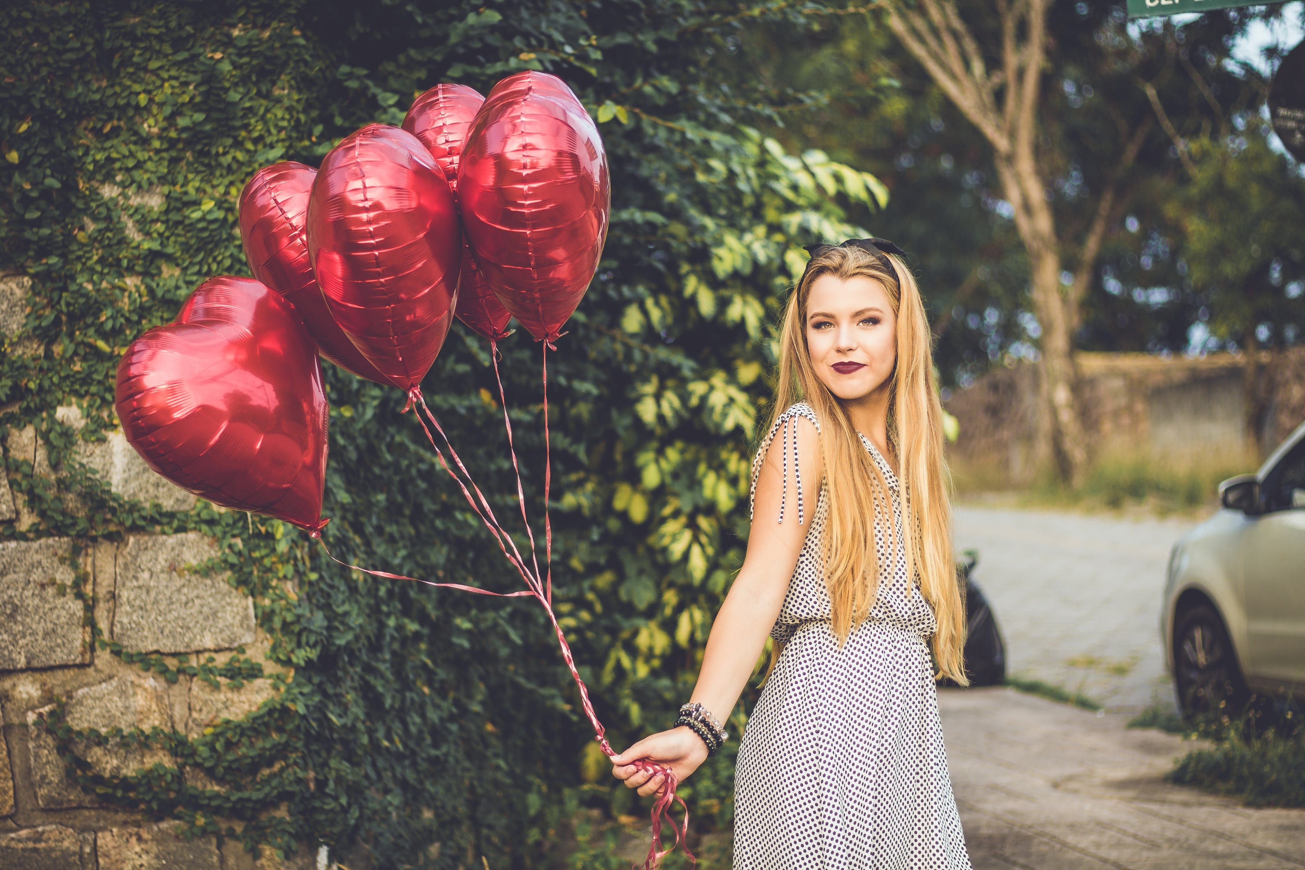 Woman Wearing Grey Dress Holding Heart Balloons