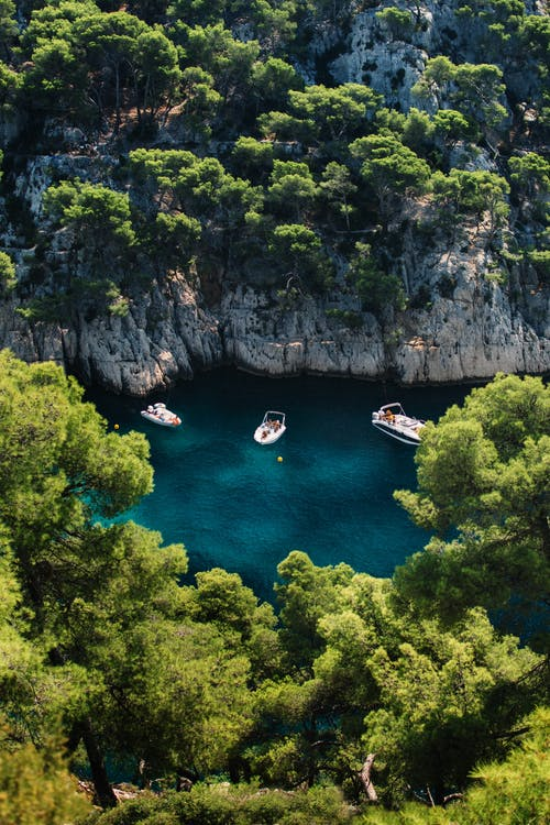 Aerial Photo of Speed Boat at Middle of Sea Surrounded by Trees