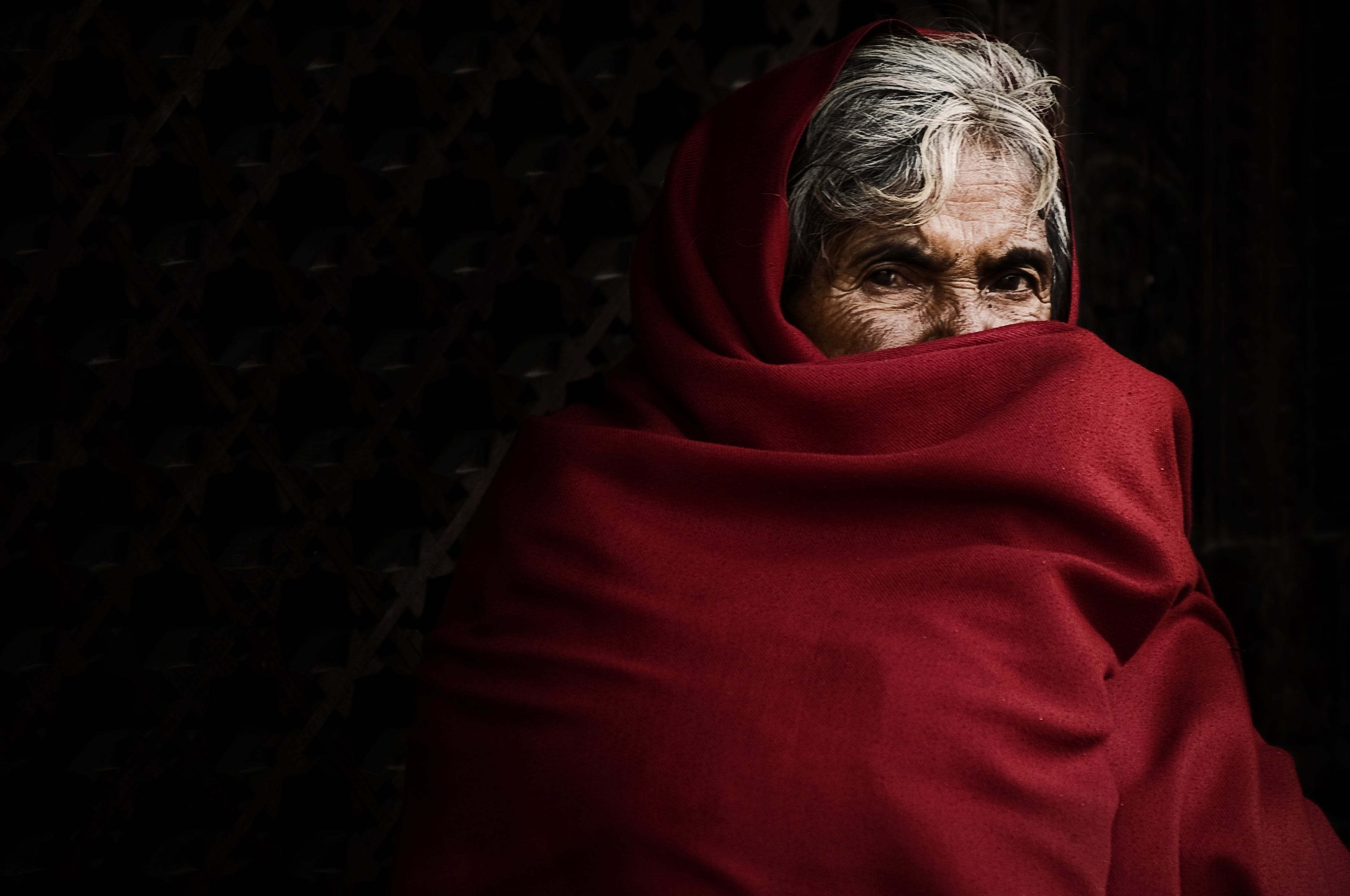 Person Covering His Face With Red Blanket
