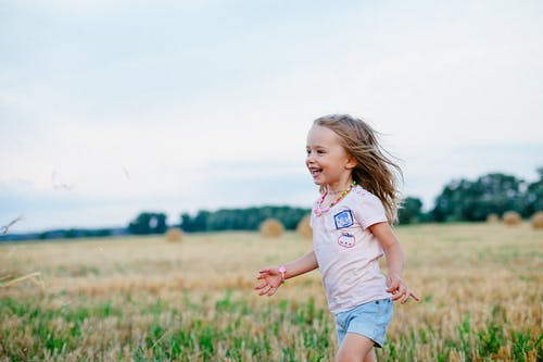 Smiling Girl Running Towards Left on Green Field