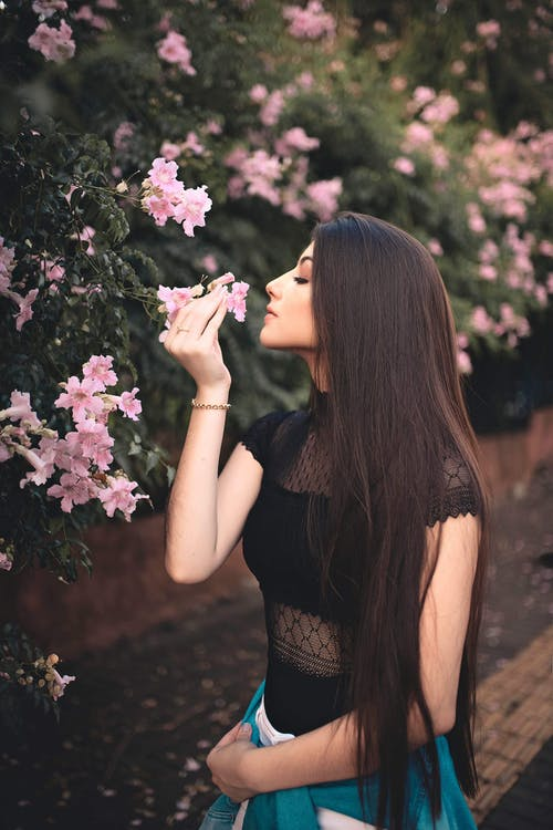 Woman Holding Pink Flower Smelling