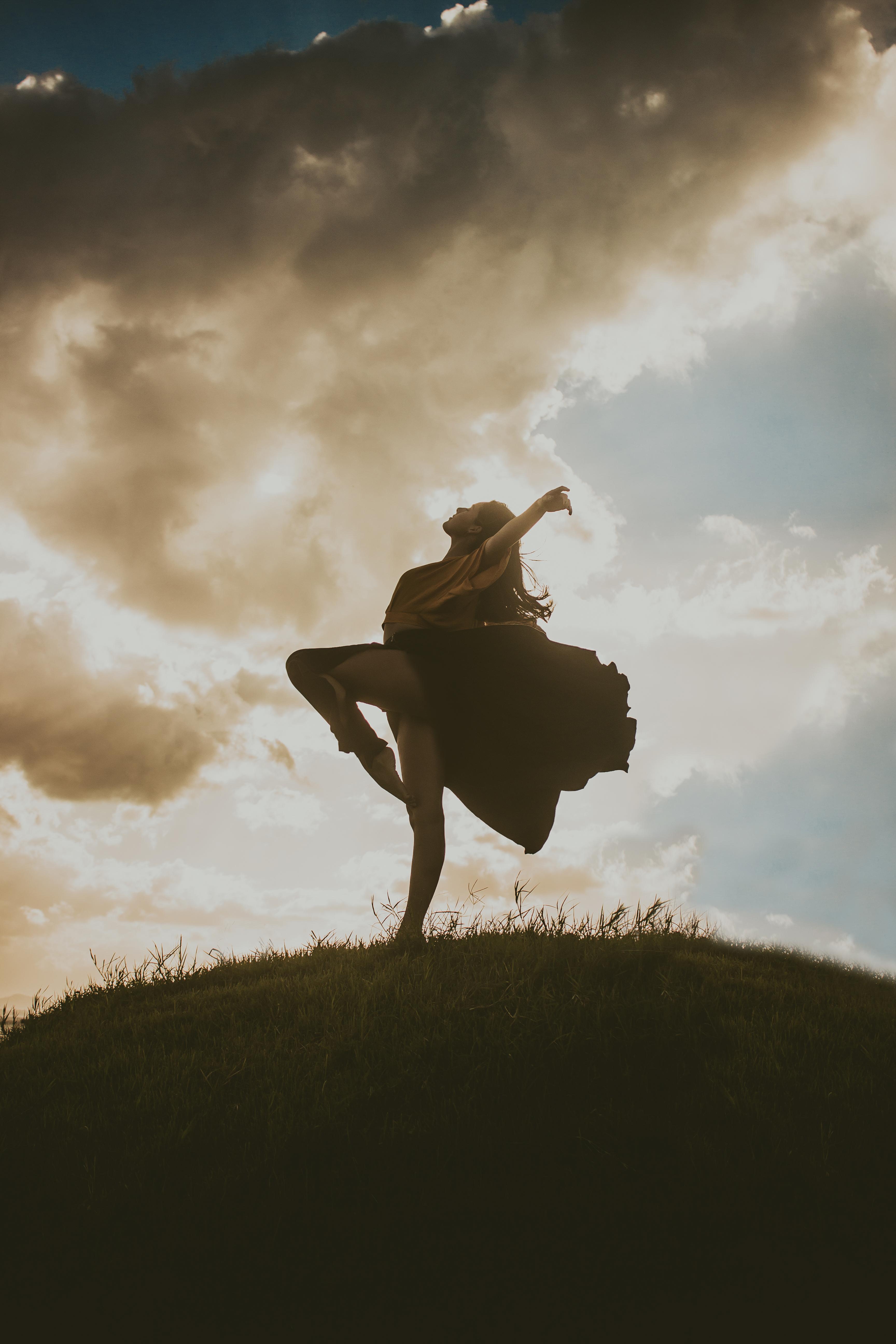 Woman Wearing Black Midi Dress Dancing on a Hill