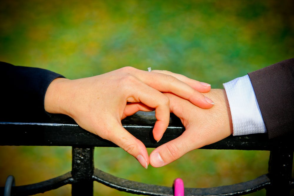 Two people holding hands. | Photo: Pexels