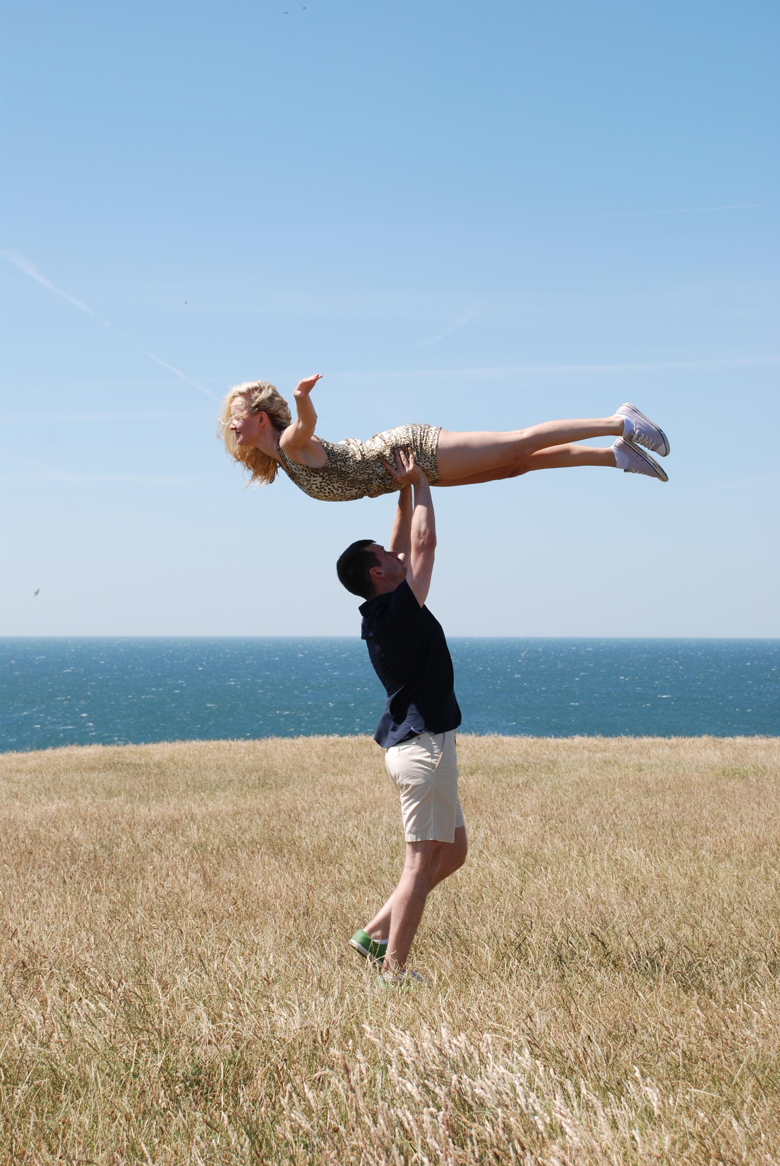 Man Lifting Woman in Open Field Near Body of Water