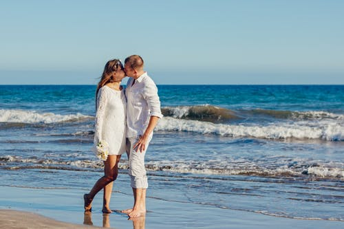 Man and Woman Kissing Near Ocean Waters