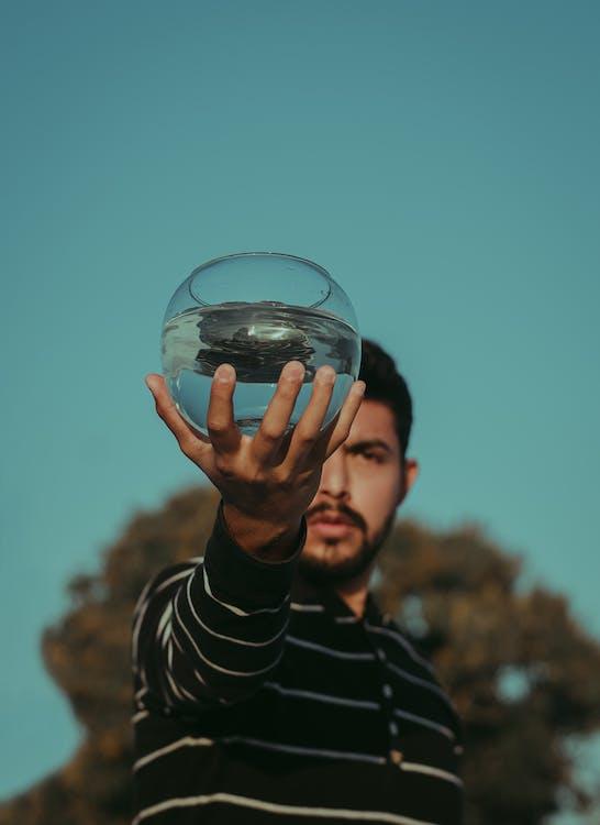 Photo of Man Holding Fish Bowl