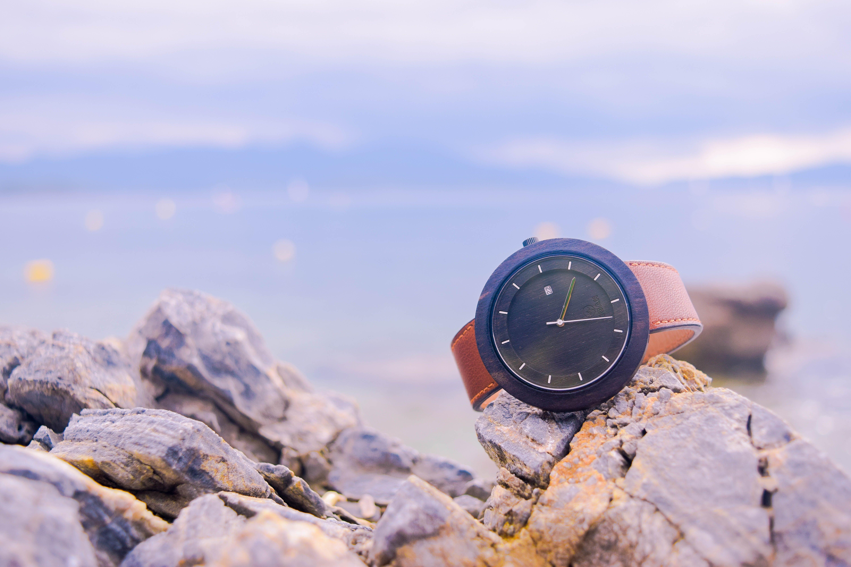 Brown and Black Round Analog Watch on Beige Rocks