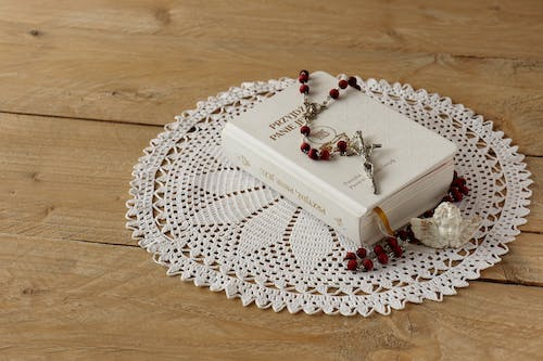 Rosary on Top of Book on Doily Mat