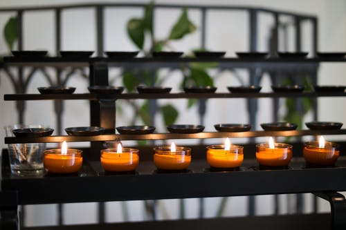 Close Up Photography of Tealight Candles on Black Metal Rack
