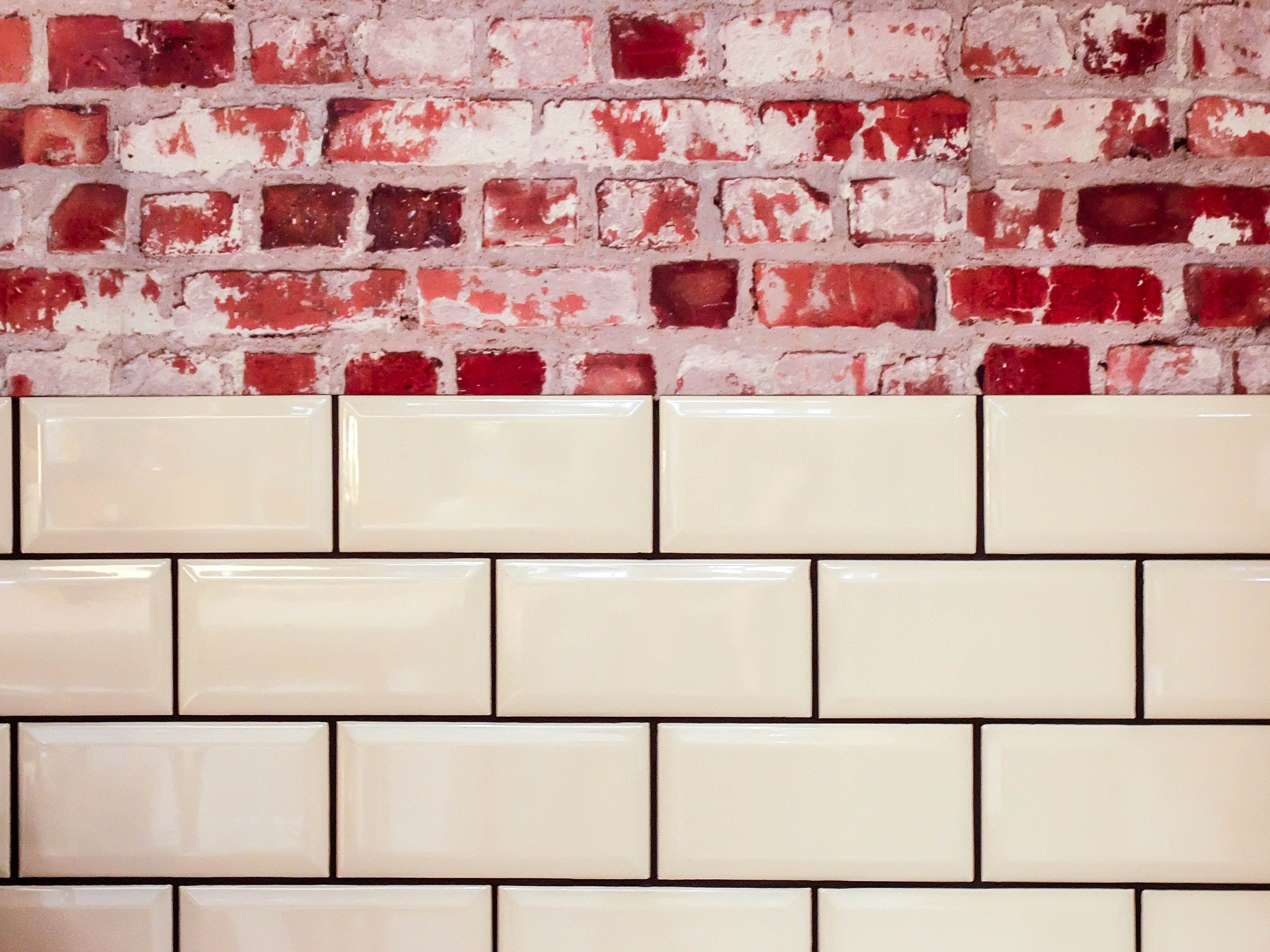 White Ceramic Wall Tile Beside Red Concrete Bricks