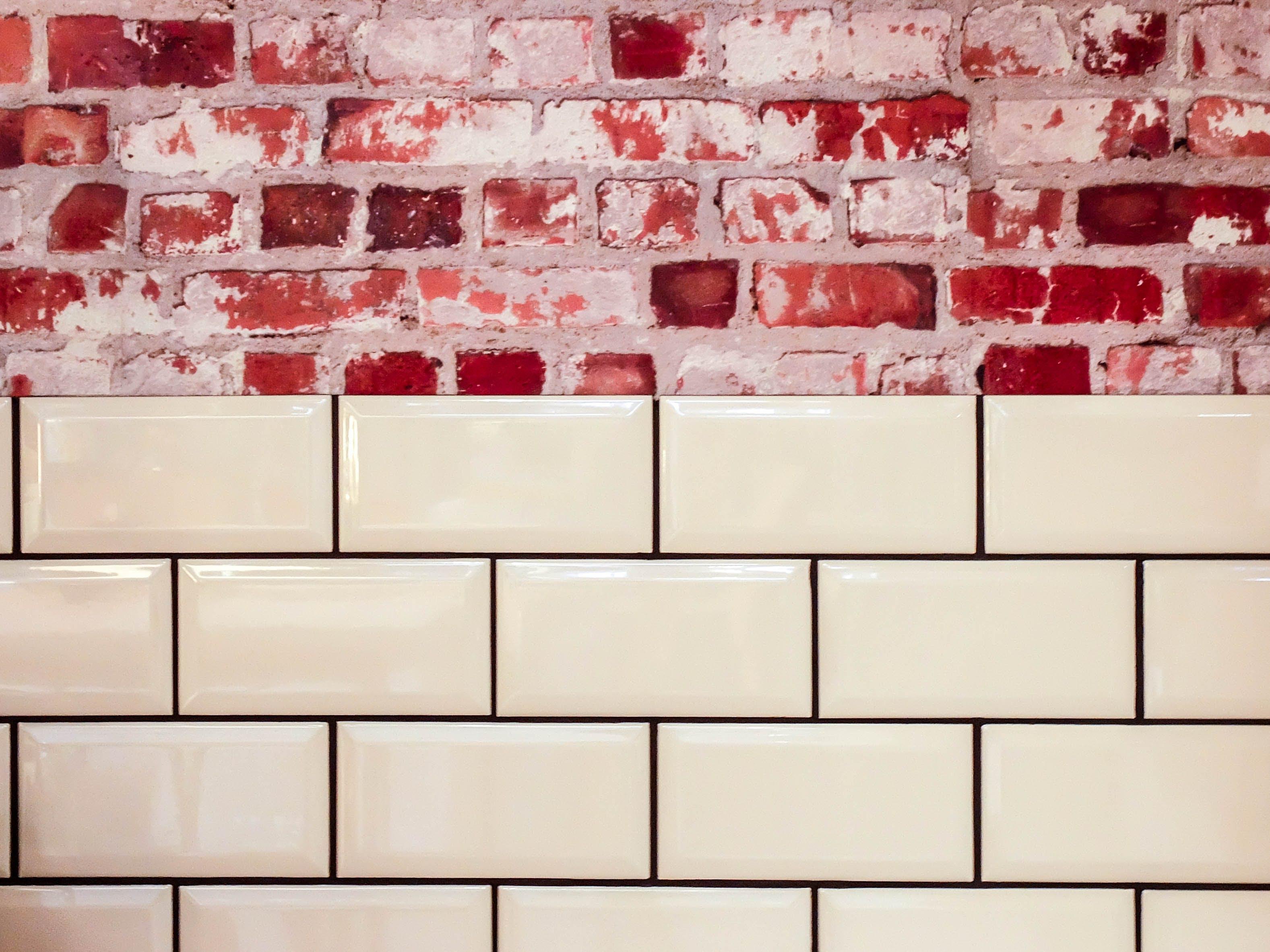 White Ceramic Wall Tile Beside Red Concrete Bricks