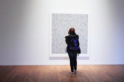 Woman Standing Infront of a Wall Mount Painting