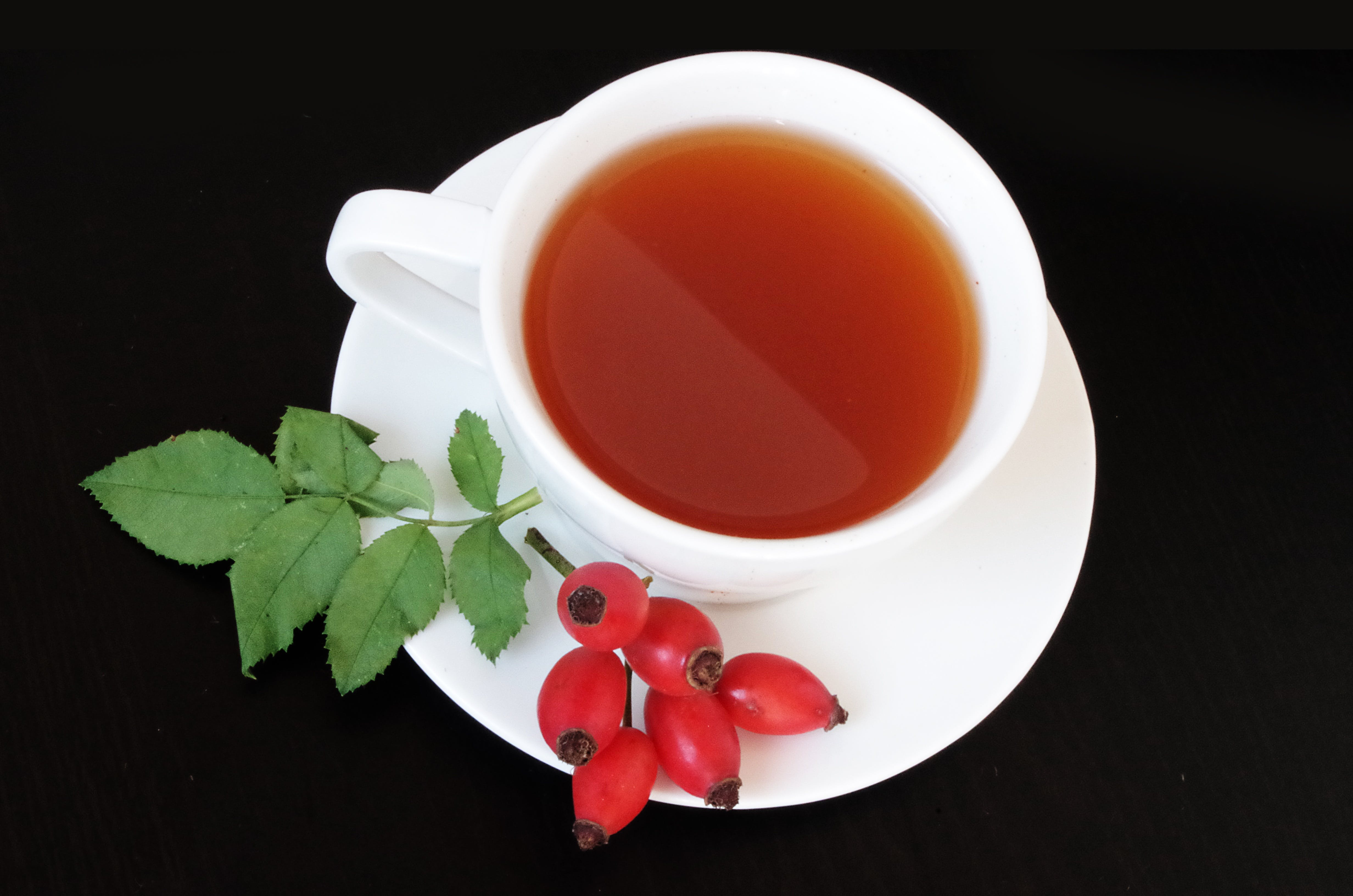 White Teacup With Red Fruits Beside