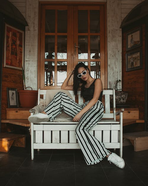 Woman in Black Tank Top and Black-and-white Stripe Pants Sitting on White Wooden Bench While Holding Head
