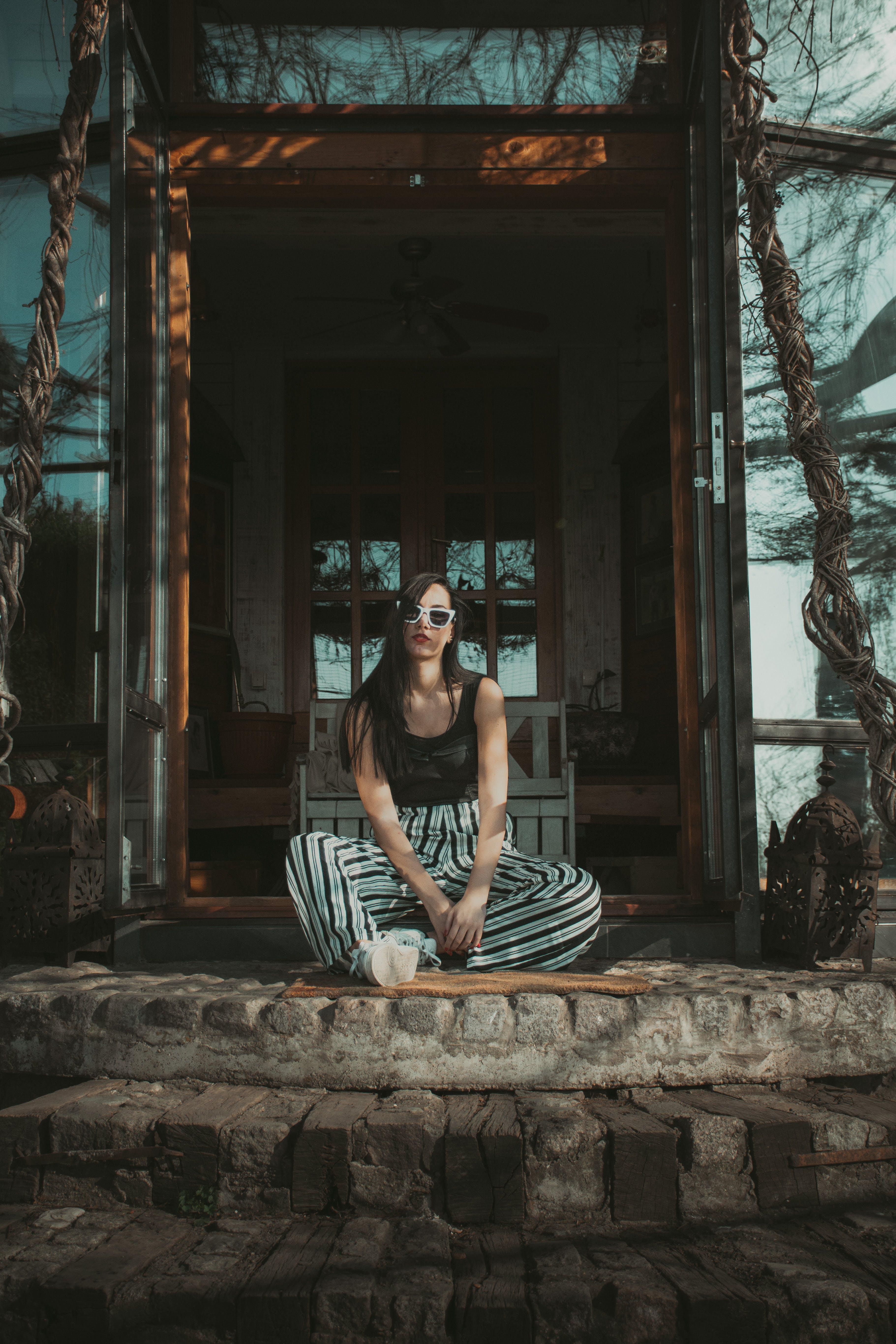 Woman Sitting Beside House