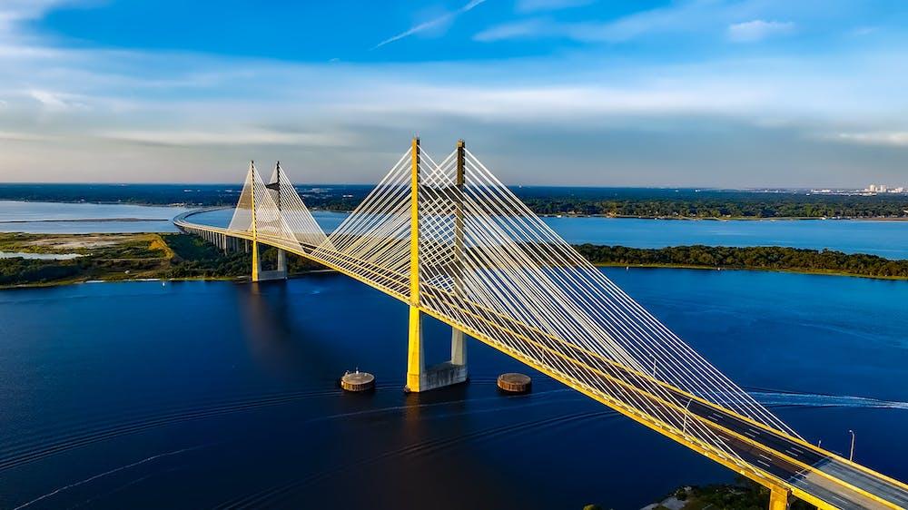 Concrete bridge on body of water. | Photo: Pexels