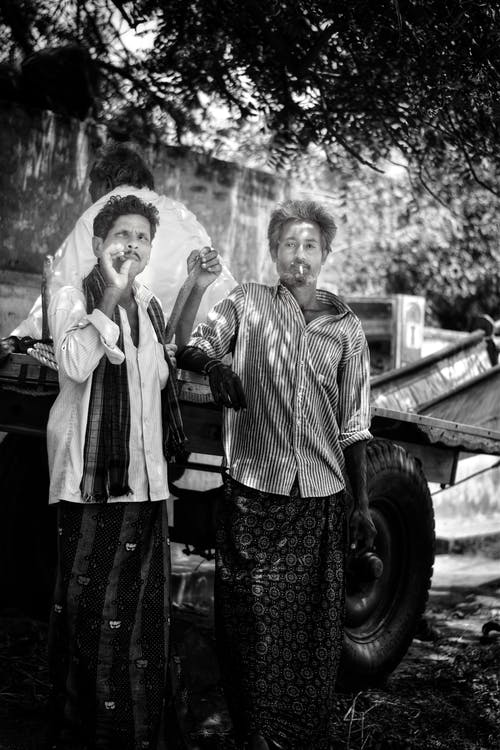Grayscale Photography of Two Men Standing Under Tree Smoking