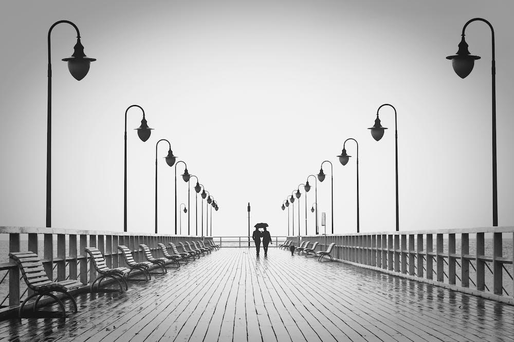 Couple walking on pier   Photo: Pexels