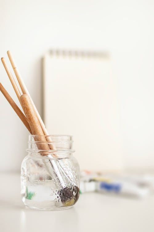 Close-Up Photo of Paintbrushes In Bottle