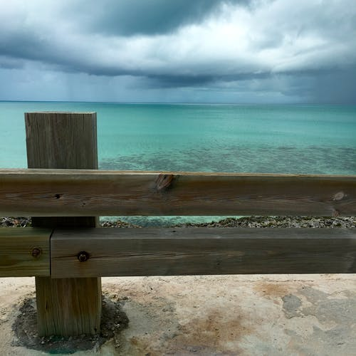 Brown Wooden Fence Near Blue Ocean Water Under White Cloudy Sky during Daytime