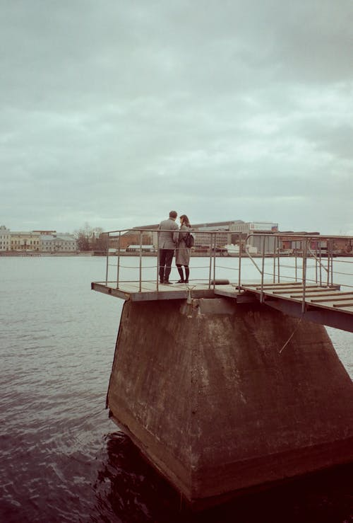 Woman and Man Standing on Dock