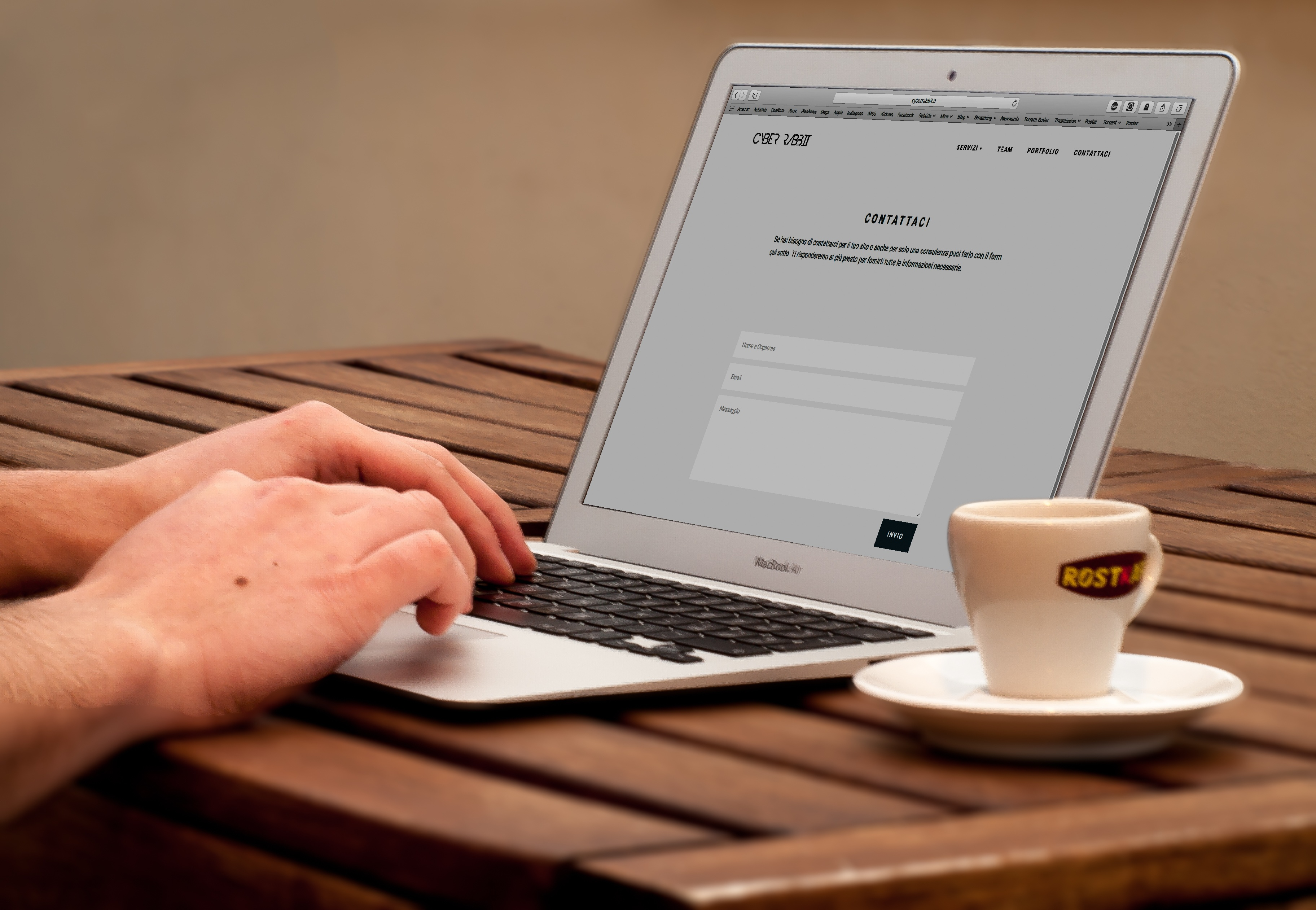 Human Using Laptop Beside Teacup on the Wooden Table