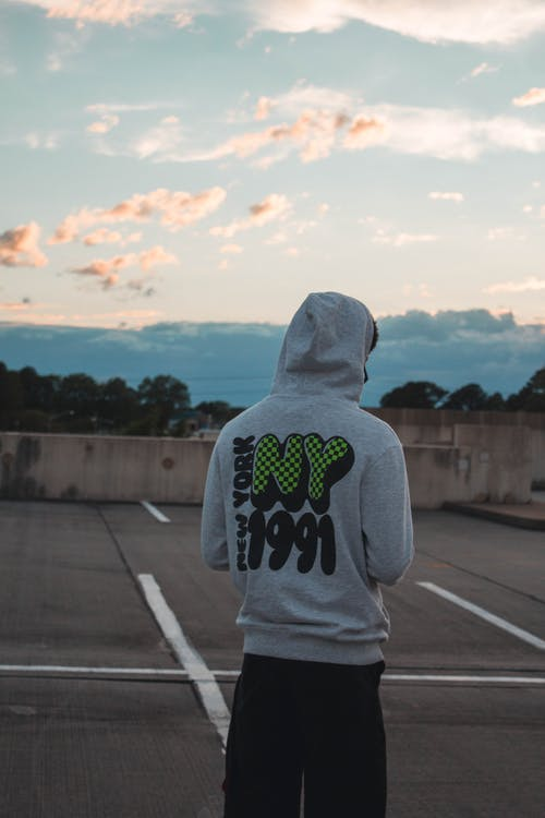 Rear view of Man Wearing Gray Pullover Hoodie and Black Pants at Parking Lot