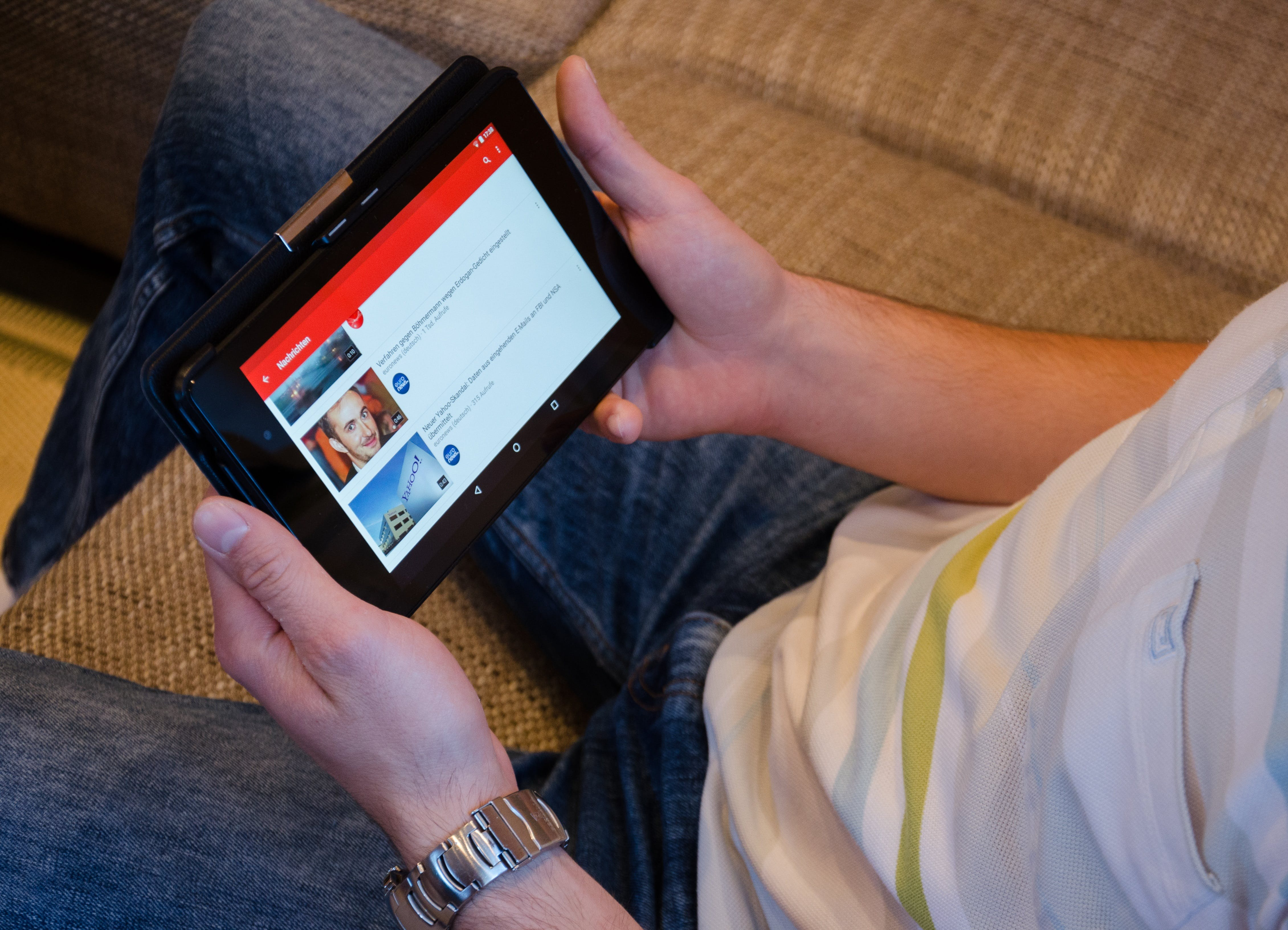 Person Holding Tablet Computer Showing Videos