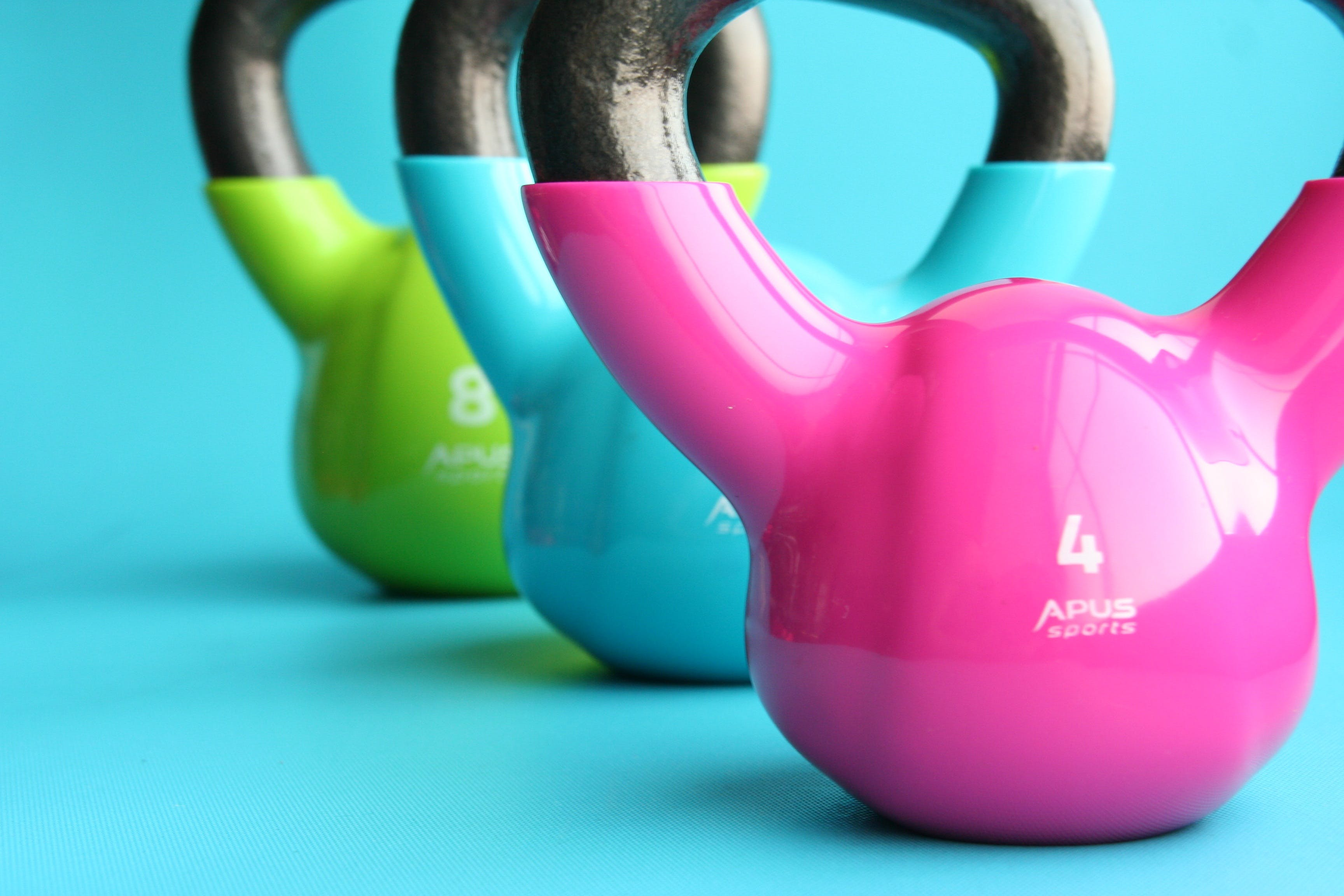 Green, Blue, and Pink Kettle Bells on Blue Surface