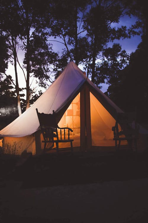 White and Brown Lighted Cabin Tent at Woods