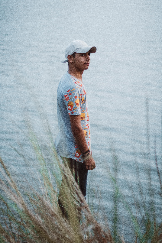 Man Wearing Gray Shirt Standing Beside Body of Water