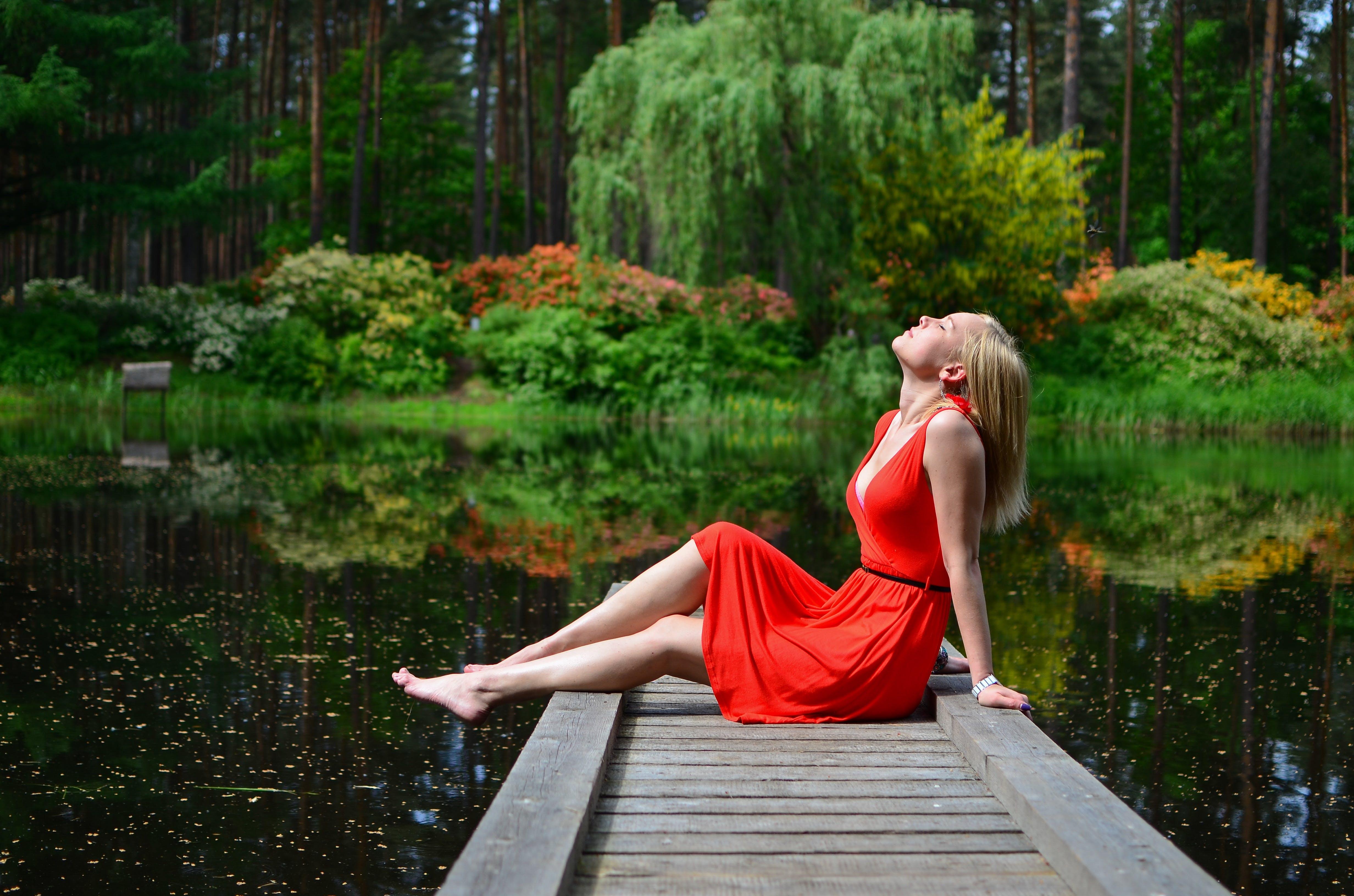 Woman Sitting on Gray Dock
