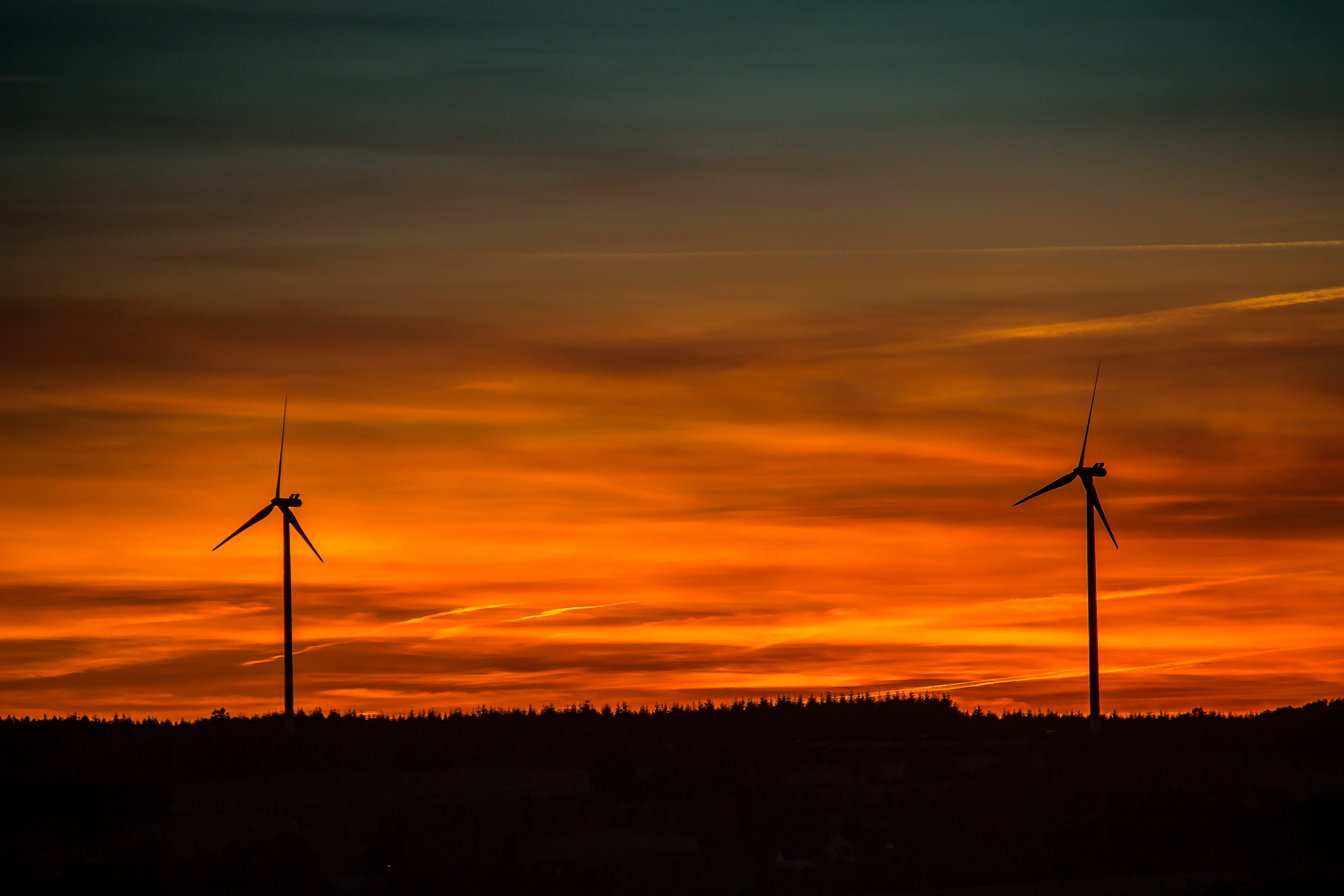 Silhouette of Windmills Under Orange Sunset
