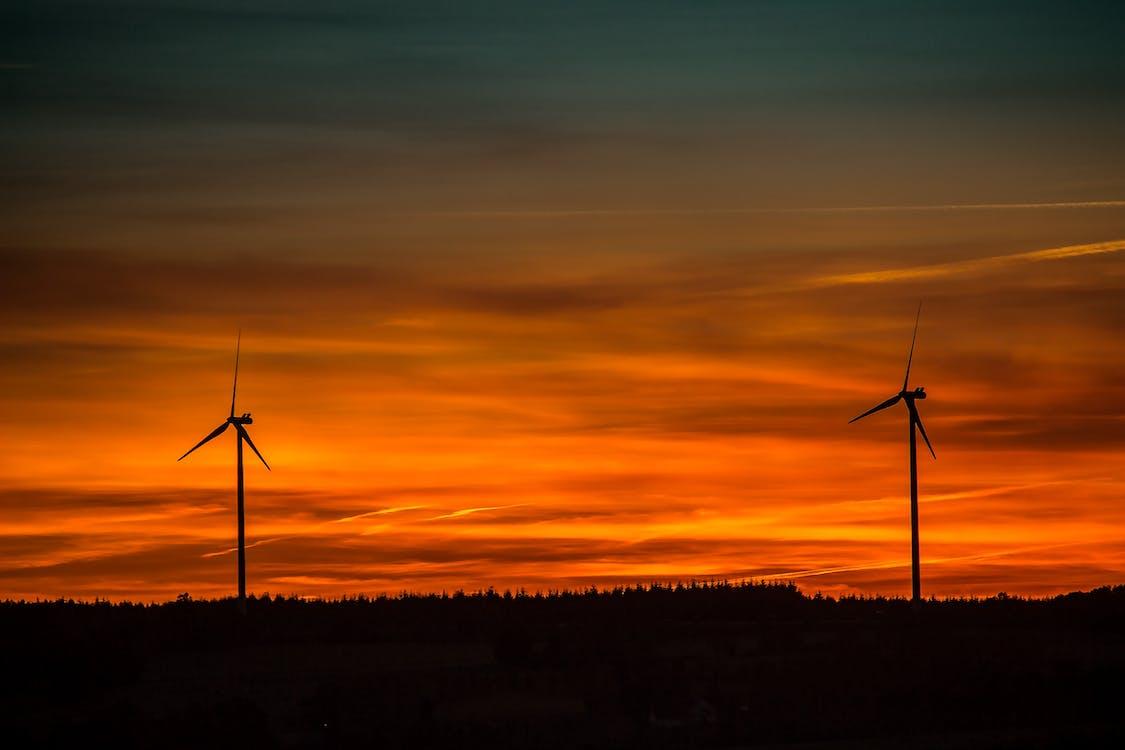 Silhouette of Windmills Under Orange Sunset