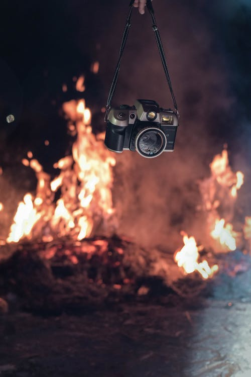 Person Holding Black and Grey Camera Near Fire