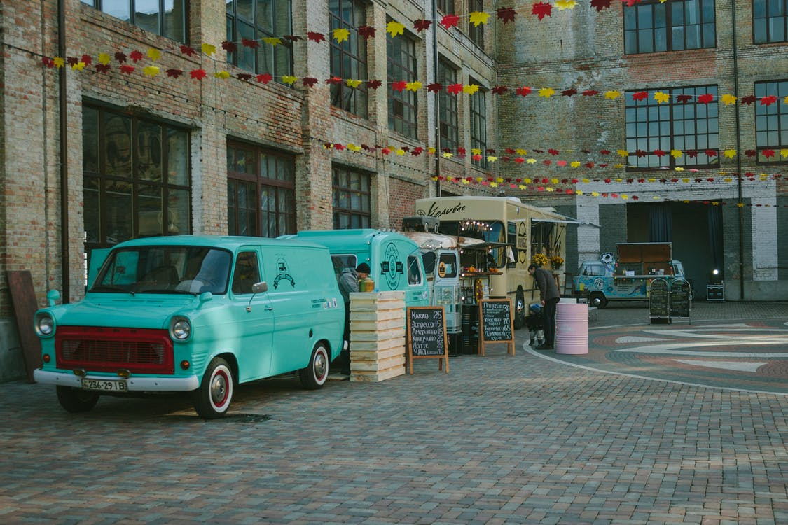 Green Minivan Near Brown Wooden Crate and Brown Food Truck