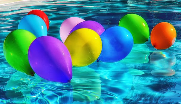 Purple Yellow and Blue Balloon on Swimming Pool
