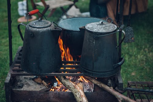 Three Black and Gray Pots on Top of Grill With Fire on Focus Photo