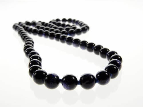 Beaded Black Necklace on White Surface