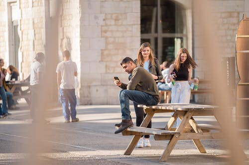 Man in Grey Long-sleeved Shirt and Blue Denim Jeans Sits on Picnic Table Near Women Walking