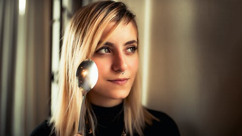 Портретное фото женщины с кольцом в носу, глядя в сторону