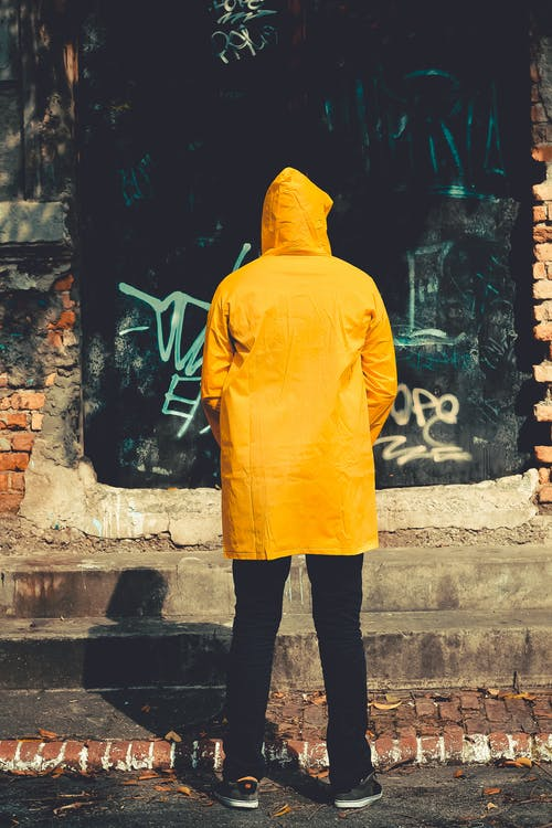 Person Standing Near Brown Structure in Yellow raincoat
