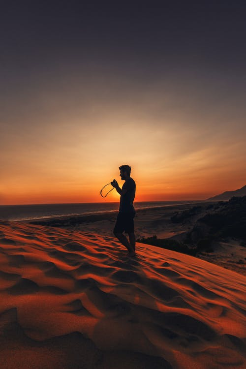 Silhouette Of Man Standing On Sand Dune