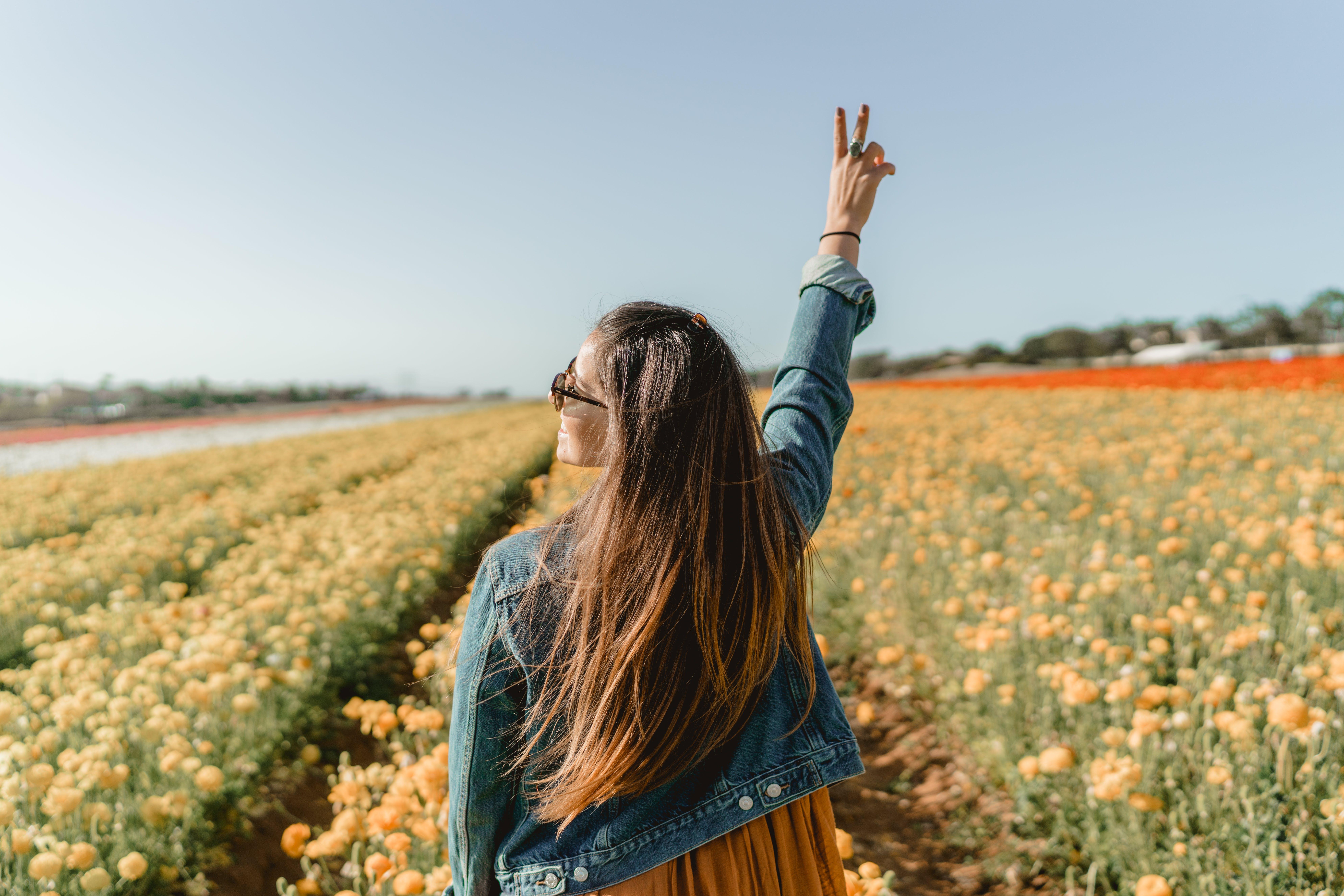 Woman Standing On Yellow Petaled Flower Garden Raising Hand